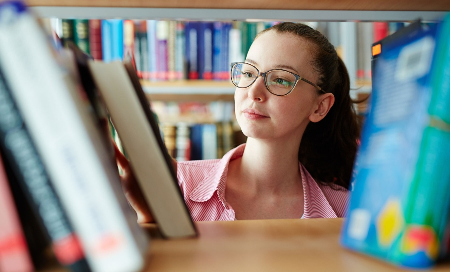 female with glasses in library